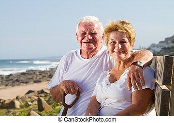 feliz, pareja mayor, en, playa, banco