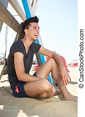 feliz, playa, joven, sentado