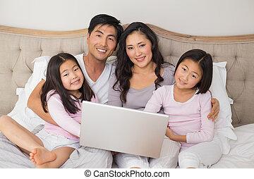 feliz, relaxado, família quatro, usando computador portátil, cama