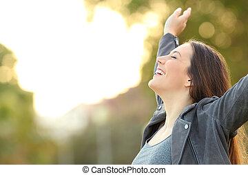 feliz, senhora, respirar, ar fresco, braços elevando, em, um, parque