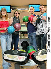 Fellows and girls stand near tenpin bowling with balls for playing bowling and laugh merrily, focus on boy on  right