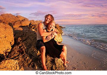 felsig, sitzen, paar, verheiratet, junger, wasserlandschaft, sonnenuntergang- strand, glücklich