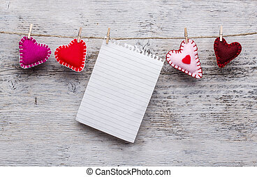 Felt handmade hearts and blank paper hanging on rope