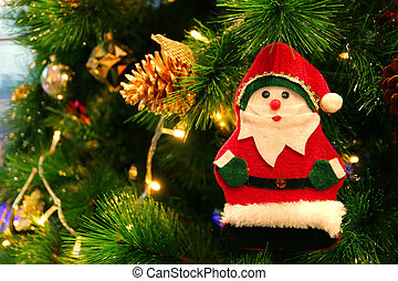 Felt Santa Claus Ornament and Gold Pine Cone Hanging on a Sparkling Christmas Tree