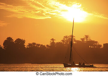 Felucca boat sailing on the Nile river at sunset, Luxor,...