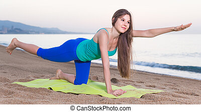 Female 20-25 years old is doing excercises on endurance on the beach near sea.