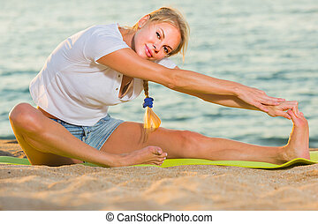 Female 20-30 years old is practicing stretching in white T-shirt on the beach near sea.