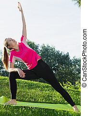 Female 20-30 years old is practicing yoga in pink T-shirt in the park.