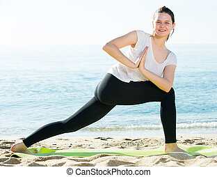 Female 20-30 years old is practicing yoga in white T-shirt on the beach near sea.