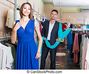 Female 25-30 years old is trying on new dark blue dress in boutique.