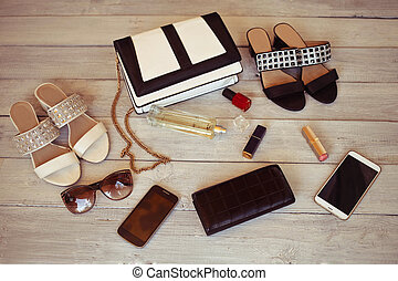 Female accessories on a white wooden background: bag, perfume, shoes, smartphone, varnish, purse and lipstick