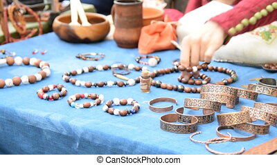 Vendor putting on the table handmade wooden bracelets. Table-top sale of wooden and bronze accessories