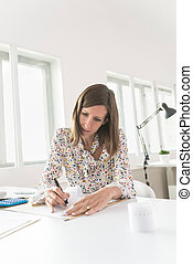 Female accountant calculating and reviewing numbers