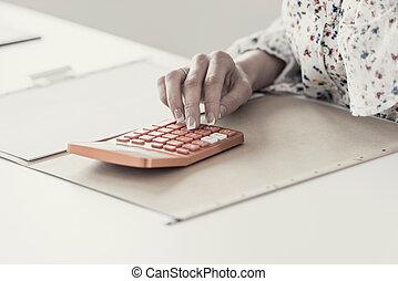 Female accountant calculating on orange desktop calculator