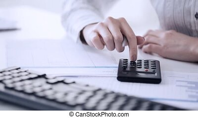 accountant making calculations and taking notes - female...
