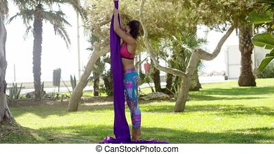 Female acrobat working outdoors on silk ribbons