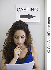 Young female studying a script under a sign saying 'casting.' Vertically framed shot.