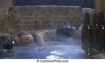 Female addict unconscious on sofa after overdose