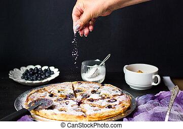 Female adding sugar to a sweet pie