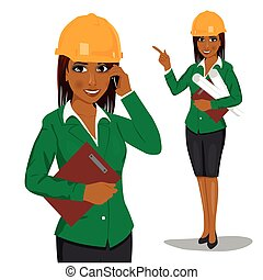 female african american architect wearing yellow safety helmet holding blueprints and clipboard talking on phone