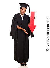female african college graduate holding arrow