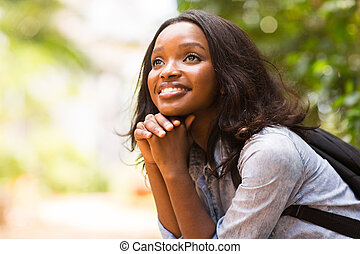 female african college student daydreaming