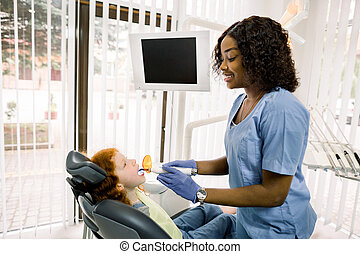 Female African dentist performing dental filling procedure to a little red haired girl in pediatric dental clinic. Doctor using dental ultraviolet curing light for filling polymerization