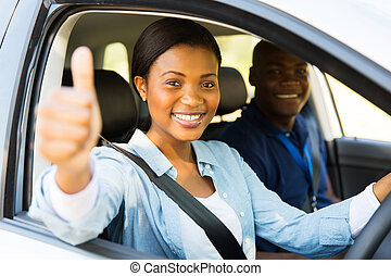 female african learner driver giving thumb up - beautiful...