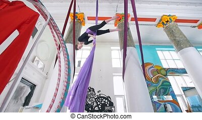 Female air gymnast flying upside down on the aerial silk in...