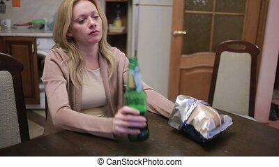 Female alcoholic dependence, woman with a bottle in hands.