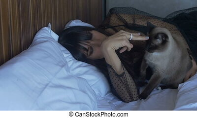 Female and cat lying on bed