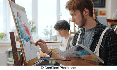 Female and male art students painting pictures during class working indoors