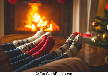 Female and male feet in wool socks warming at fireplace at...