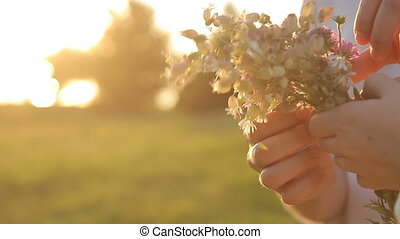 Female and male hands holding wild flowers bouquet