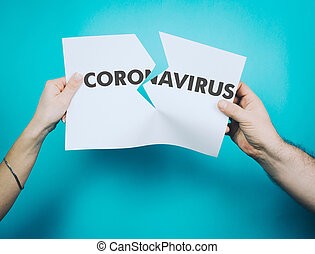 Female and male hands tear off a white sheet of paper with the word coronavirus. Covid-19 concept we are not afraid. We will beat you