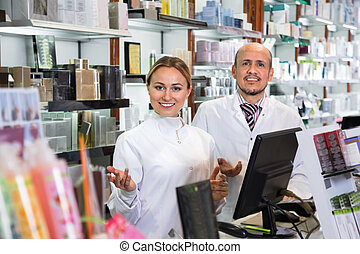 Female and male pharmacists working the pharmaceutical store