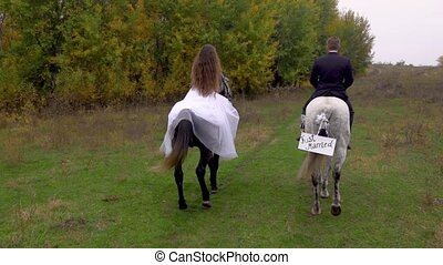 Female and male riding two horses. Just married. Back view.