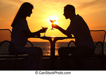Female and man's silhouettes on sunset sit at table with two...