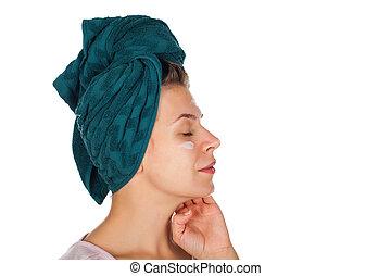 Female applying face moisturizer