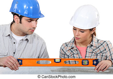 female apprentice and carpenter using ruler