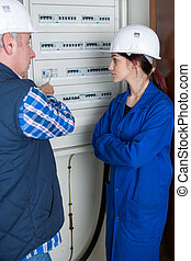 female apprentice electrician checking fuse box