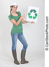 female apprentice holding recycling logo