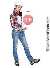 female apprentice holding stop sign