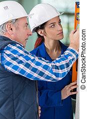 Female apprentice learning to use spirit level