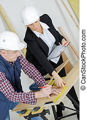 female architect and carpenter at construction site