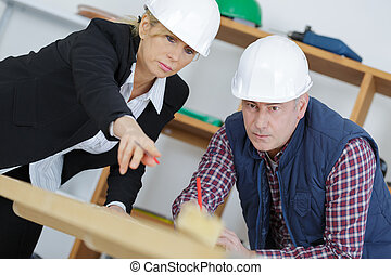 female architect and construction worker looking at scale model