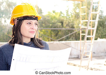 Female architect at a construction site with blueprints.