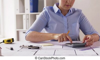female architect counting on calculator at office
