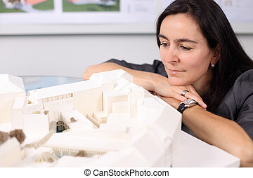 Female Architect Looking At Architectural Model
