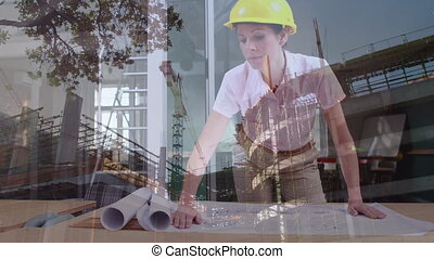 Female architect looking at blueprints with construction site
